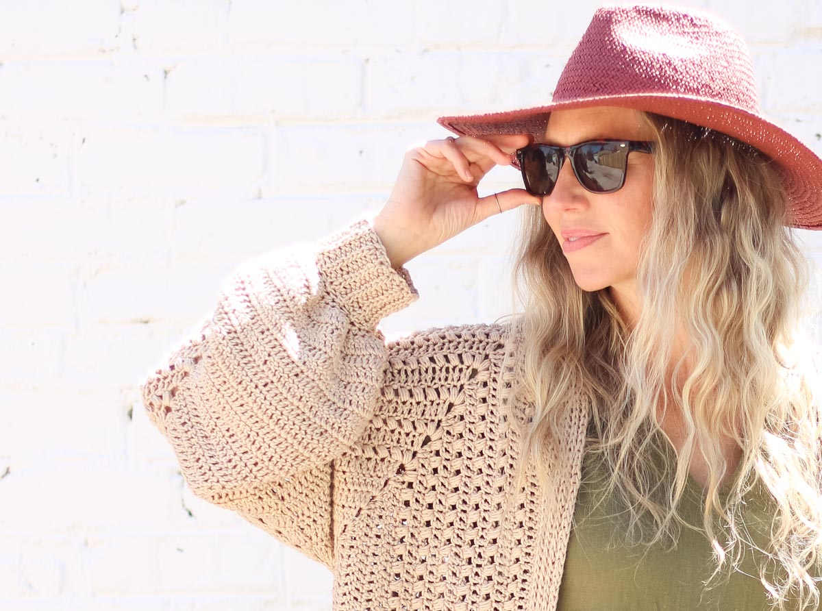 """A blonde woman wearing a floral dress and a crochet hexagon cardigan made with Lion Brand Coboo in the color """"Mauve."""""""