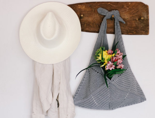 A crochet tote bag made from simple squares hanging from a rusted wood hook.
