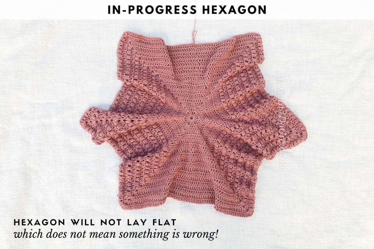 An overhead shot of a crochet hexagon that will form the basic of a crochet hexagon cardigan.