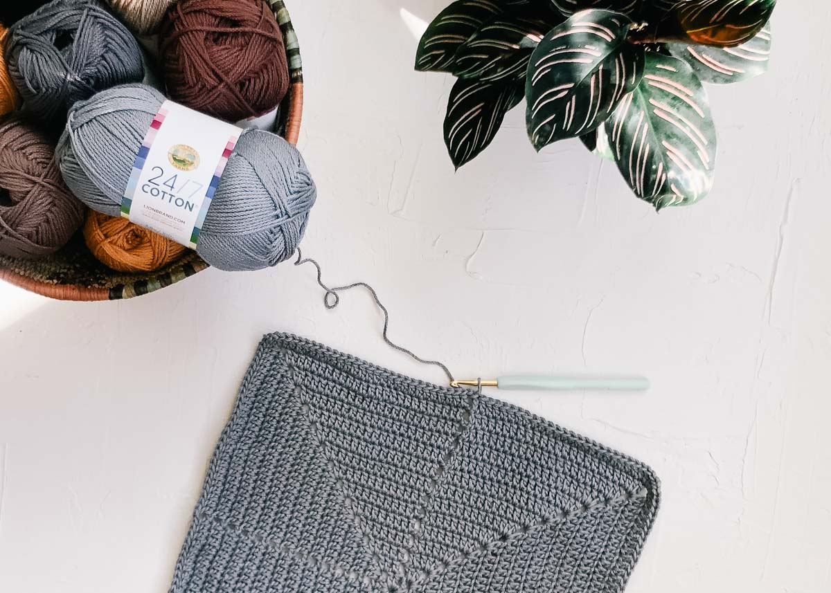 An in-progress crochet square made with Lion Brand 24/7 Cotton laying on a white table.