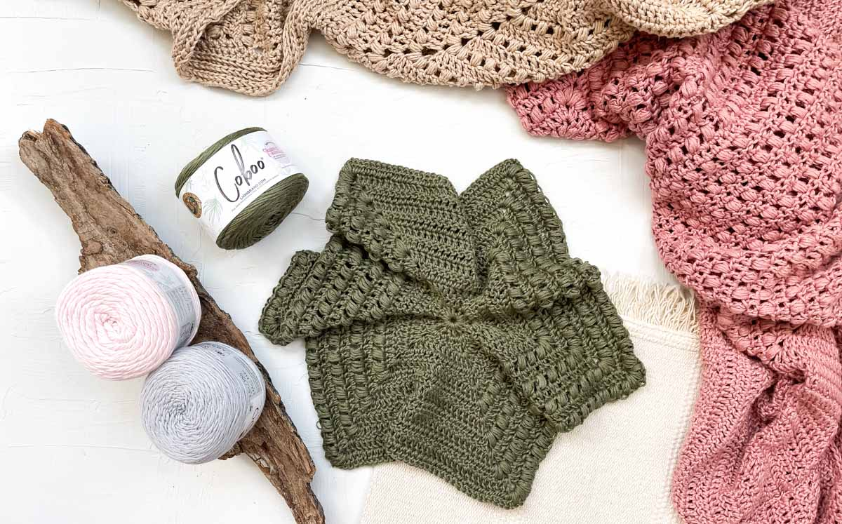 A WIP crochet hexagon sweater surrounded by a few balls of Lion Brand Coboo yarn and some sweaters that are also made from Coboo yarn.