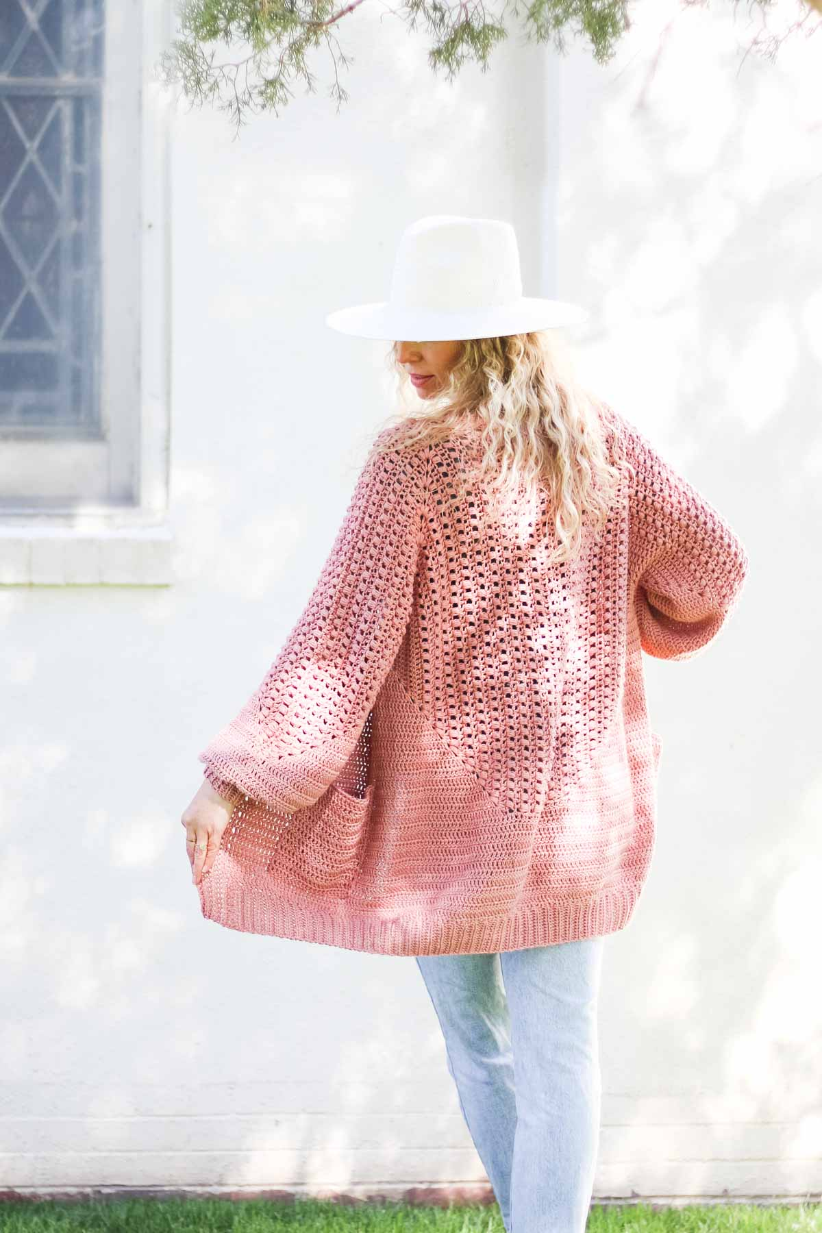 """View from the back of a blonde woman wearing a linen dress and a crochet hexagon cardigan made with Lion Brand Coboo in the color """"Mauve."""""""