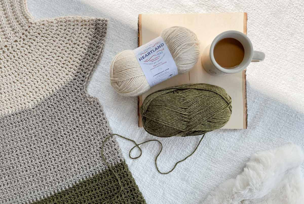 An in-progress photo of a turtleneck sweater made of Lion Brand Heartland yarn. The photo shows what the sweater body looks like before the sleeves are attached.