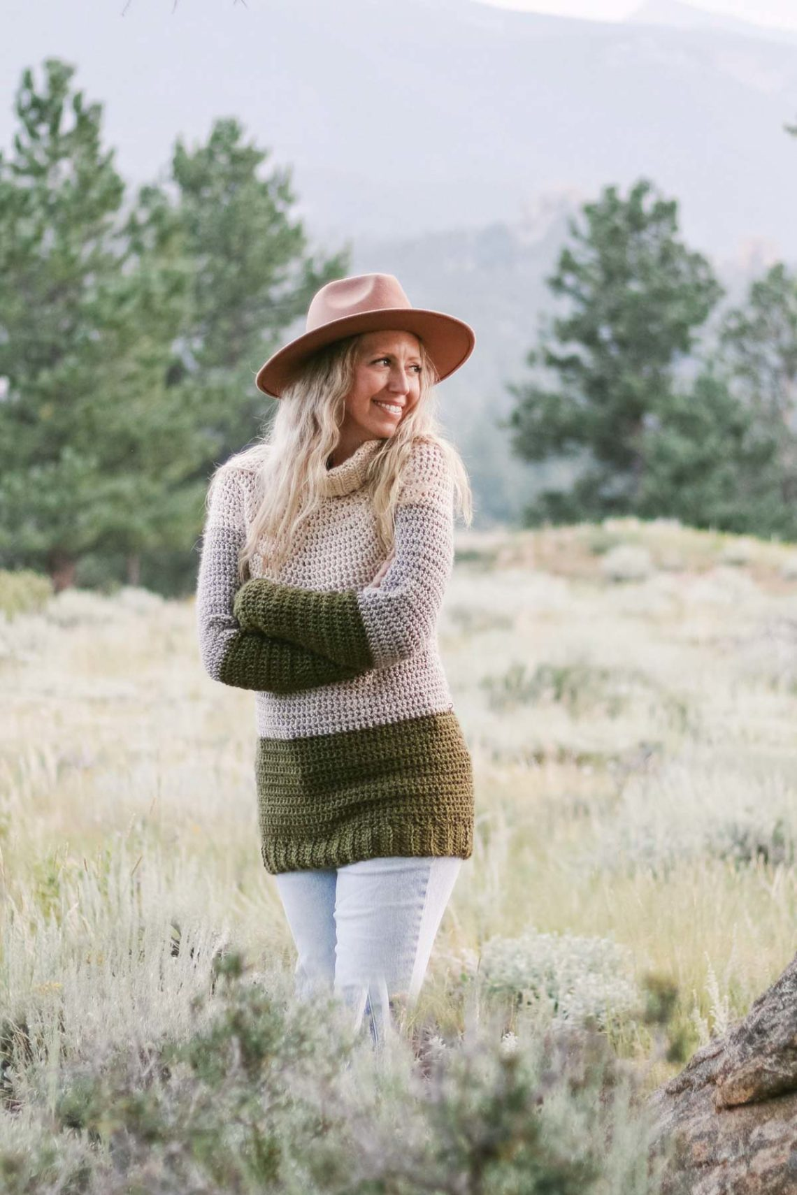 Woman standing in the mountains wearing a crochet yoke sweater pullover.